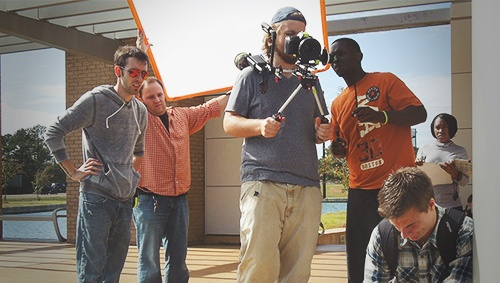 group of film students with camera equipment filming