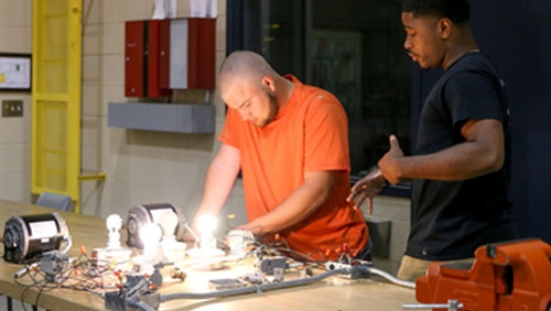 two students working with electrical connections